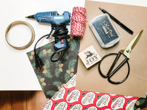 supplies needed to make a double-sided paper mason jar ring ornament including two kinds of Christmas scrapbooking paper, a holiday stamp and black ink stamp pad, scissors, hot glue and a mason jar ring