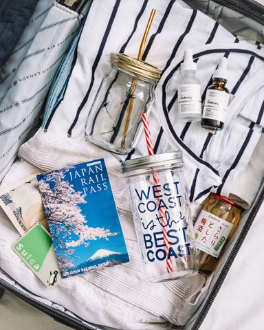 close up shot of carry on suitcase with travel documents and glass mason jar tumblers