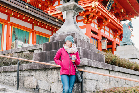 woman in pink jacket holding mason jar tumbler in front of a temple in Tokyo Japan
