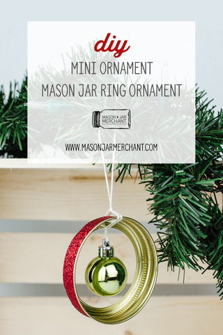 small green Christmas ornament hanging in a mason jar ring rimmed with red glitter hanging from an evergreen bow