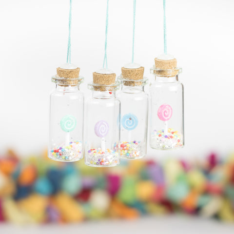 set of four handmade Christmas ornaments with tiny pastel colored lollipops and confetti tucked inside small glass bottles with cork lids