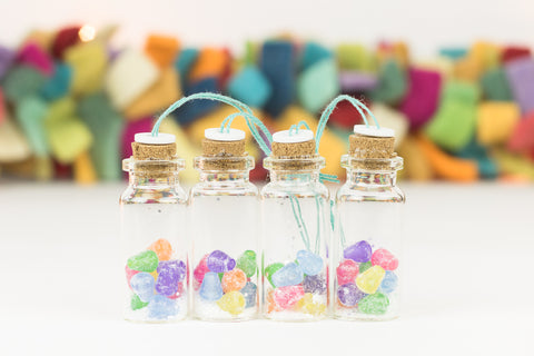 set of four handmade mini glass bottle ornaments filled with brightly colored gumdrops