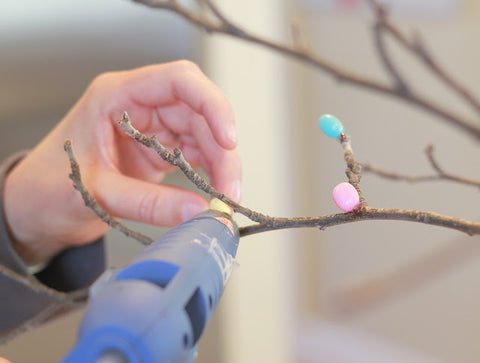 Woman hot gluing pastel colored jelly beans on to twigs to make an Easter tree from Crafty Sisters