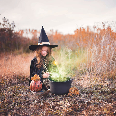 Girl in a witch costume stirring a boiling cauldron source: Unsplash