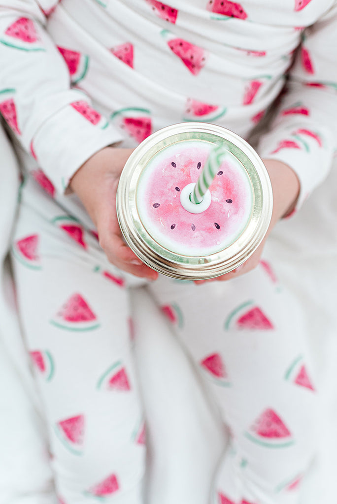 small boy wearing pjs covered in bright pink and green watercolour watermelons and holding a reusable mason jar tumbler with a straw lid that looks like a slice of watermelon