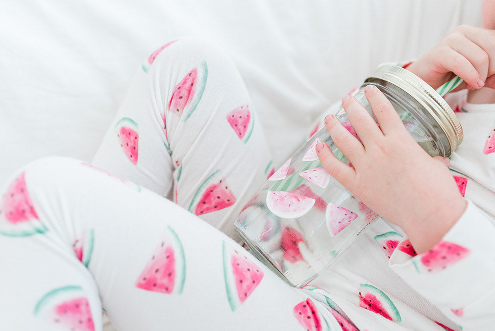 young child in watermelon pjs lounging on a white blanket and drinking water from a reusable glass mason jar tumbler with a straw
