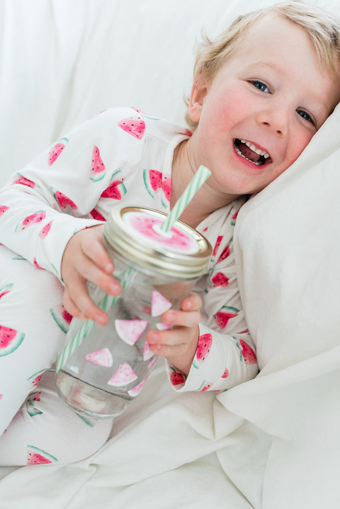 blond boy with a big grin wearing watermelon pyjamas and holding a matching watermelon reusable mason jar tumbler with a straw