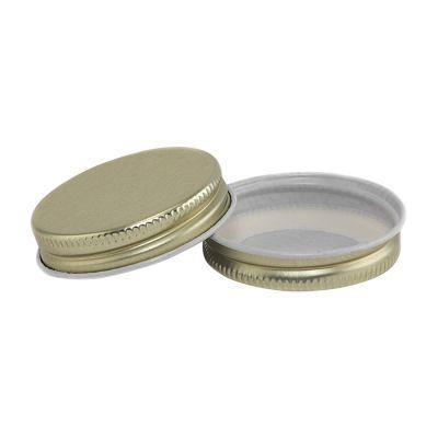 two gold mini canning jar lids on a white background
