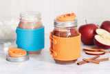 two 16 oz reusable glass mason jars with silver and orange sippy cup lids. both jars have a silicone sleeve on them, one is blue and the other is orange