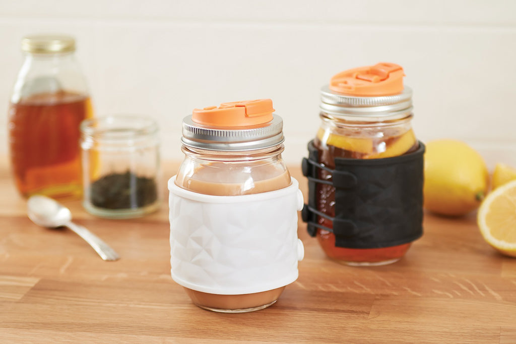 Two glass mason jars sit on a wooden counter top. They both have silver regular mouth lids with orange sippy mouth pieces, and both jars have a rubber sleeve on them, one white and one black