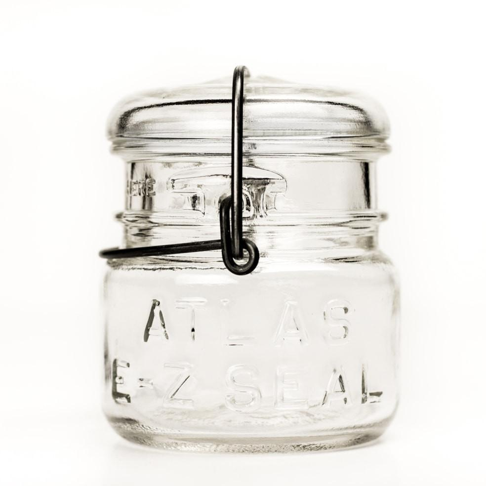 Vintage half-pint Atlas E-Z Seal jar with wire bail and glass lid, against a white background