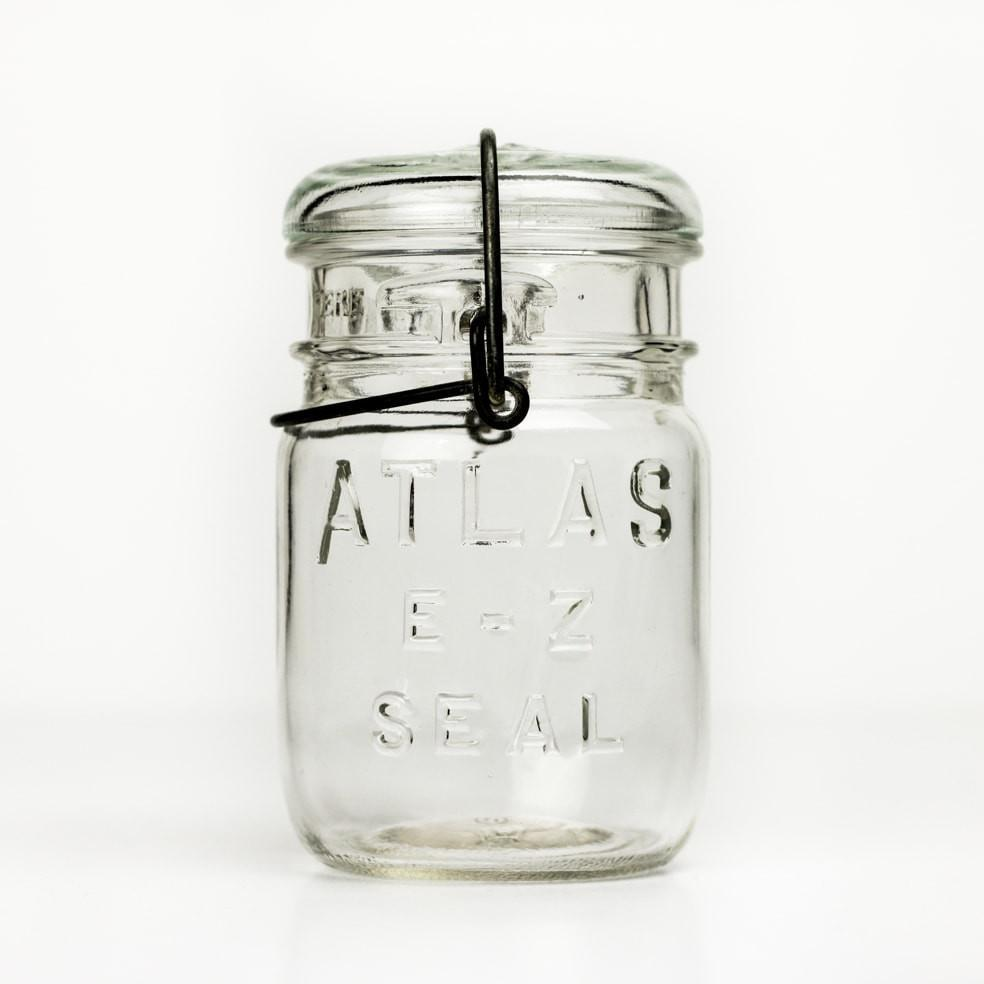 Vintage 3/4 pint Atlas E-Z Seal mason jar with wire bail and glass lid, against a white background