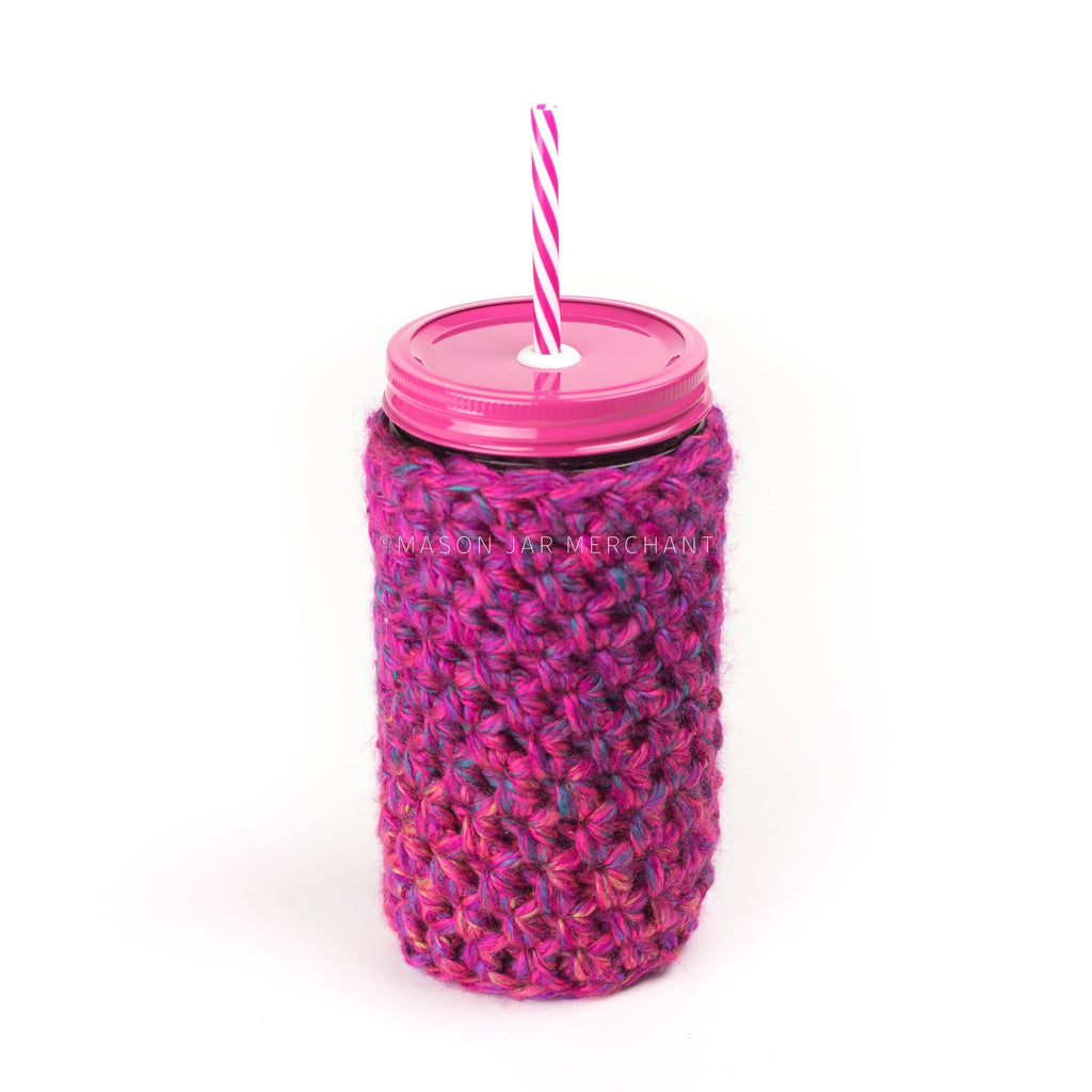24 oz reusable glass mason jar tumbler with pink straw lid and pink & white reusable straw. Pink cozy with flex of blue, green & yellow covers the jar