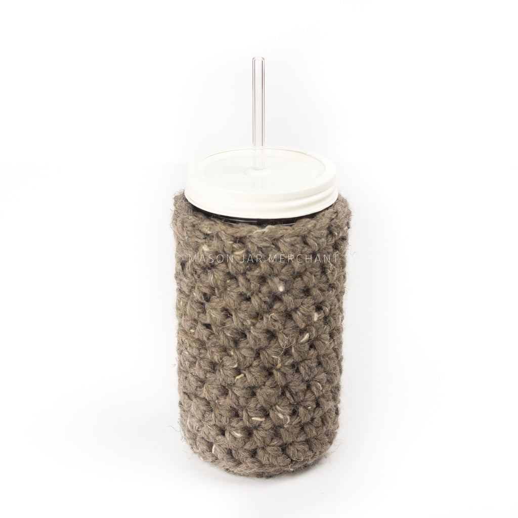 24 oz reusable glass mason jar tumbler with white straw lid and reusable glass straw. Beige brown knit cozy covers the jar