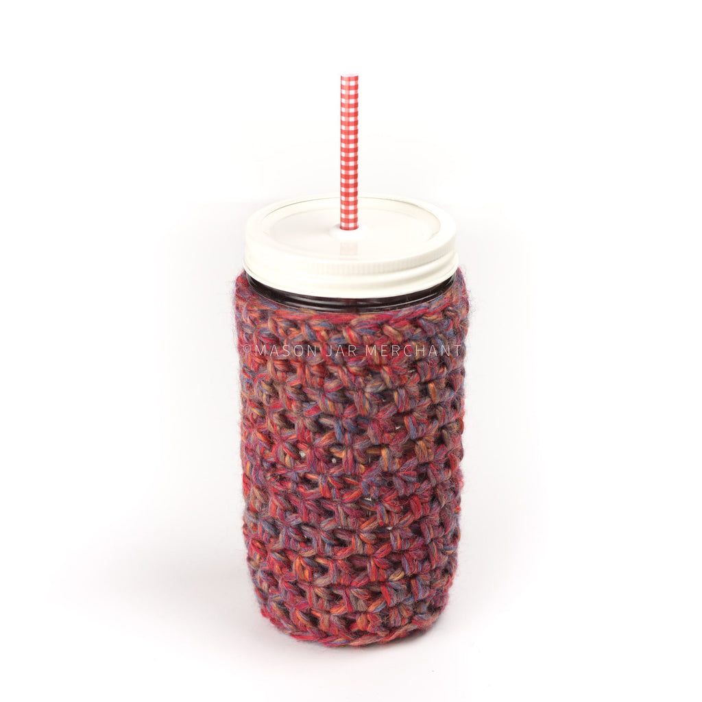 24 oz reusable glass mason jar tumbler with cream coloured straw lid and a red and white gingham reusable straw. A red, with flew of yellow and blue, knit cozy covers the jar