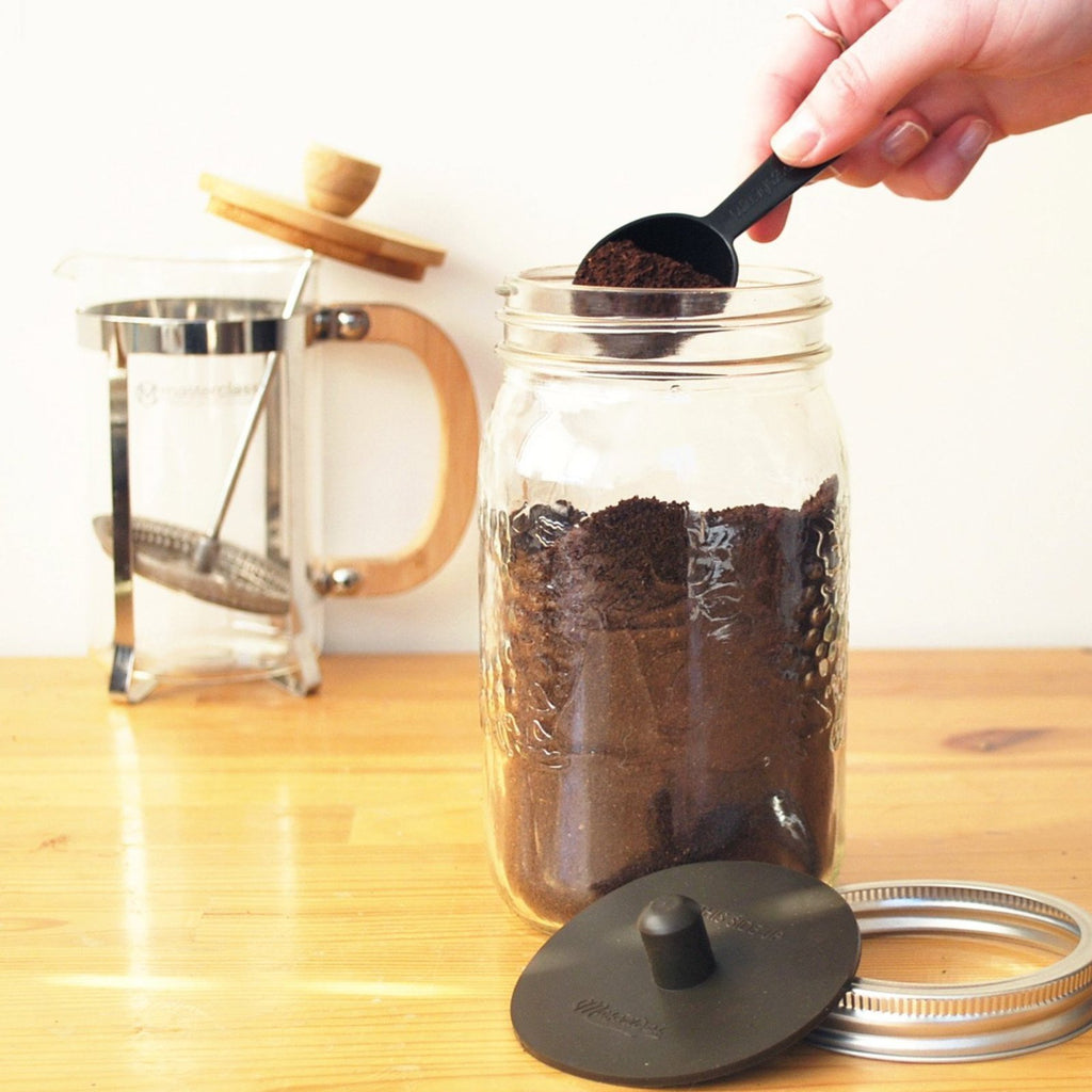 Coffee Grounds in a mason jar on a wooden countertop with the MasonTops Coffee Caps featured alongside.