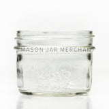 Wide mouth half-pint mason jar with a fruity logo on it.
