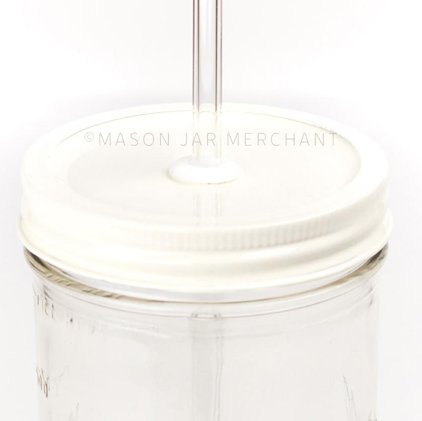 A close up picture of an all white straw lid on a 24 oz reusable glass mason jar with a reusable glass straw
