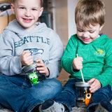 two brothers grinning and playing with the reusable straws in their little monster reusable water bottles