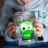 little boy drinking from reusable glass water bottle with purple and white striped straw and a bright green monster on it