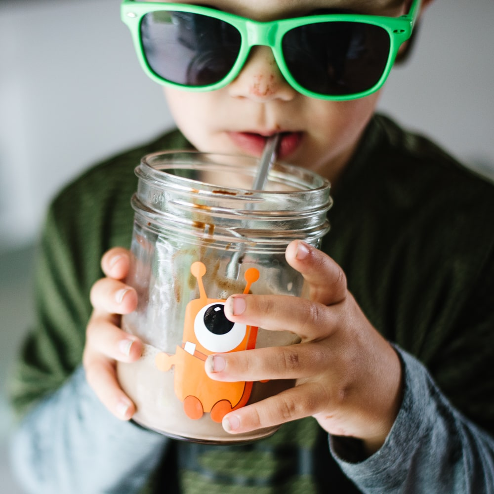 little boy wearing green sunglasses and drinking chocolate milk from a glass mason jar with a cute orange monster on it