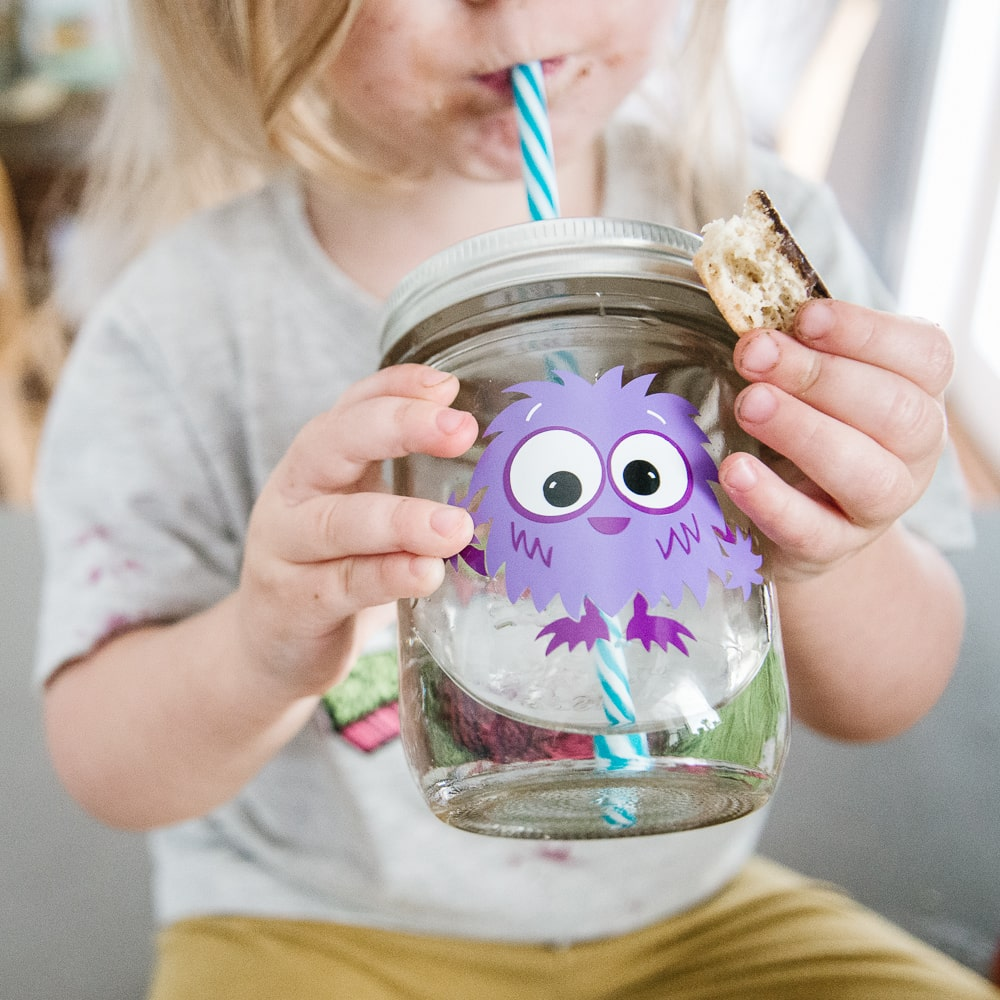 little girl drinking water out of a 16 oz reusable glass mason jar tumbler with a cute purple monster on it