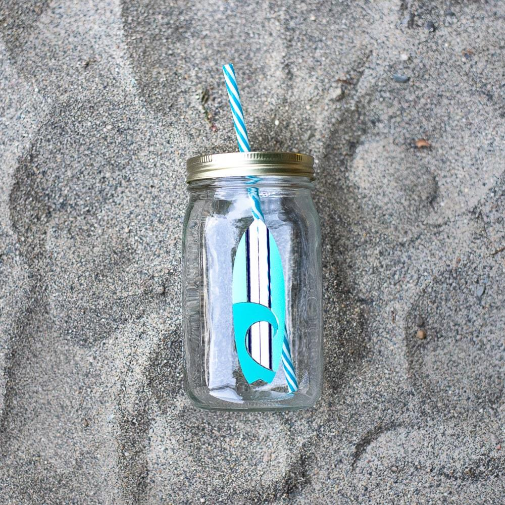 blue and white surfboard image on a reusable mason jar tumbler with a blue and white reusable straw laying on the sand