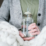 young woman in a cozy cardigan with a chunky knit blanket holding a reusable glass water bottle with the word NOPE on it