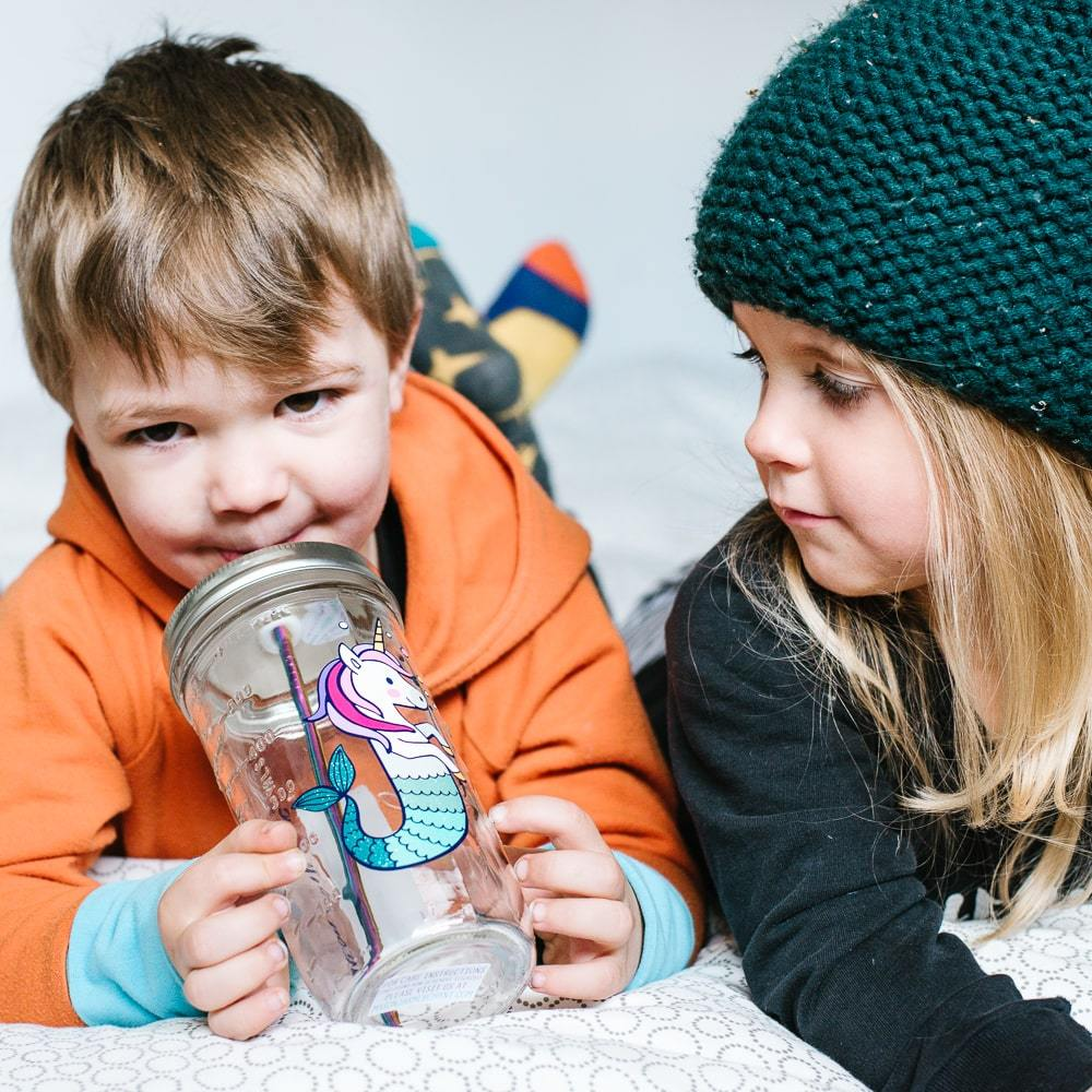 little boy and little girl sitting next to each other drinking water from a reusable water bottle with a cute unicorn mermaid on it