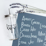 reusable glass water bottle with the words be still and know next to grey silicone placemat and sprigs of dried lavender