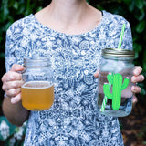 women in a shirt with a white and grey print holding a mason jar beer glass and a reusable water bottle with a cute green cactus on it Photo Credit @kimnorcross