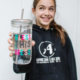 young girl in a black sweatshirt holding a reusable glass tumbler with the words bless this mess Photo Credit @kimnorcross