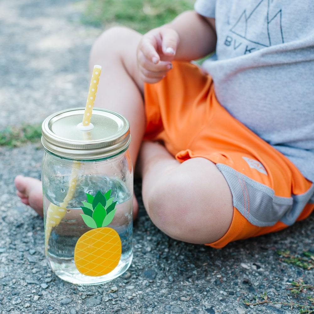 toddler in orange shorts sitting on concrete next to a bright yellow pinapple reusable water bottle