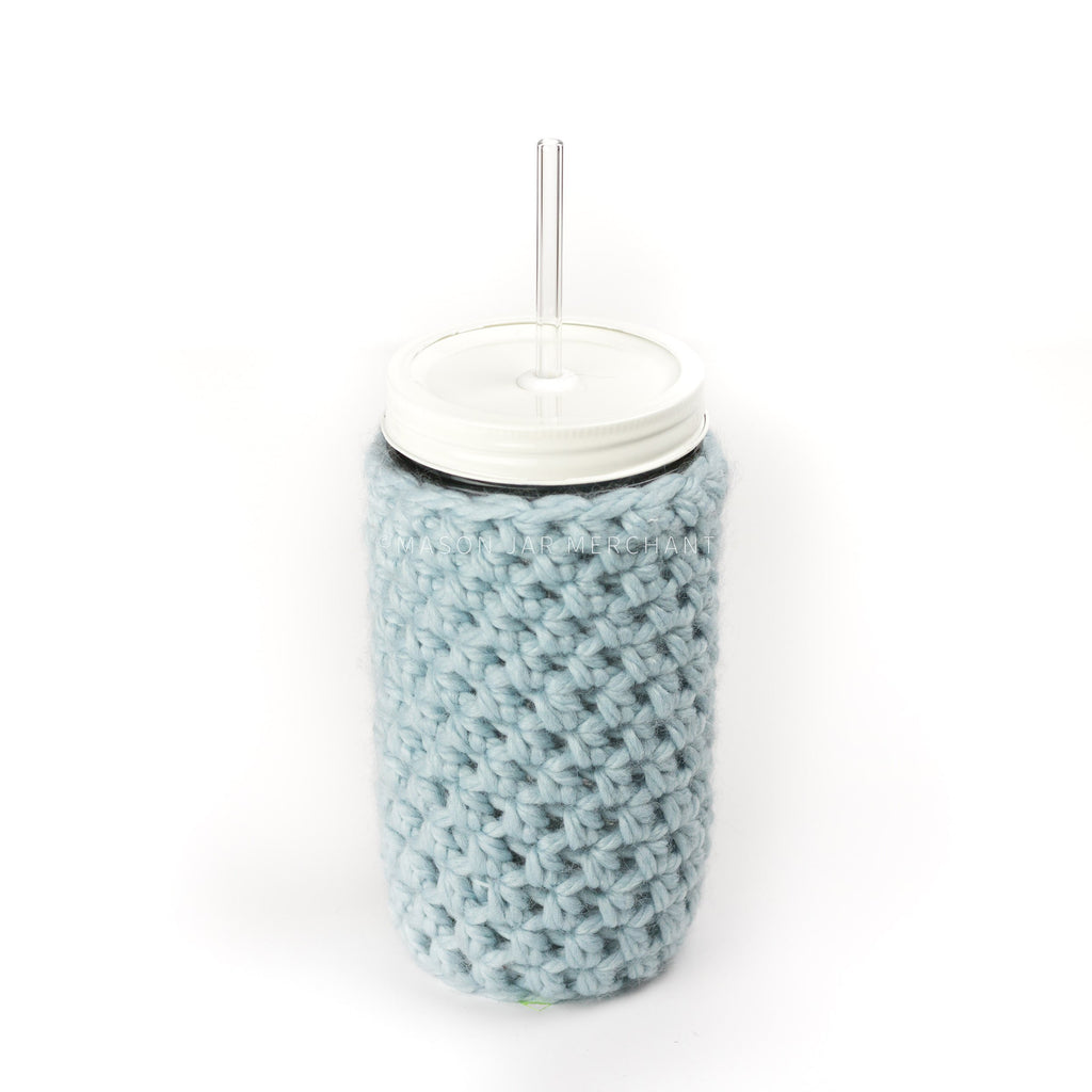 24 oz reusable glass mason jar tumbler with an all white straw lid and a glass reusable straw. A light blue knit cozy covers the jar