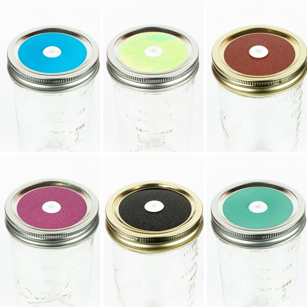 a variety of 6 glitter regular mouth mason jar straw lids in different colours on glass reusable mason jars on a  white background