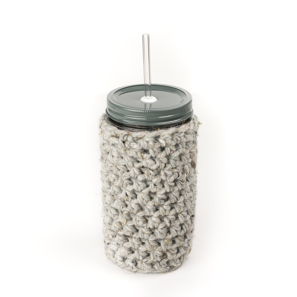 24 oz reusable glass mason jar tumbler with an all grey straw lid and a glass reusable straw. A light grey knit cozy covers the jar
