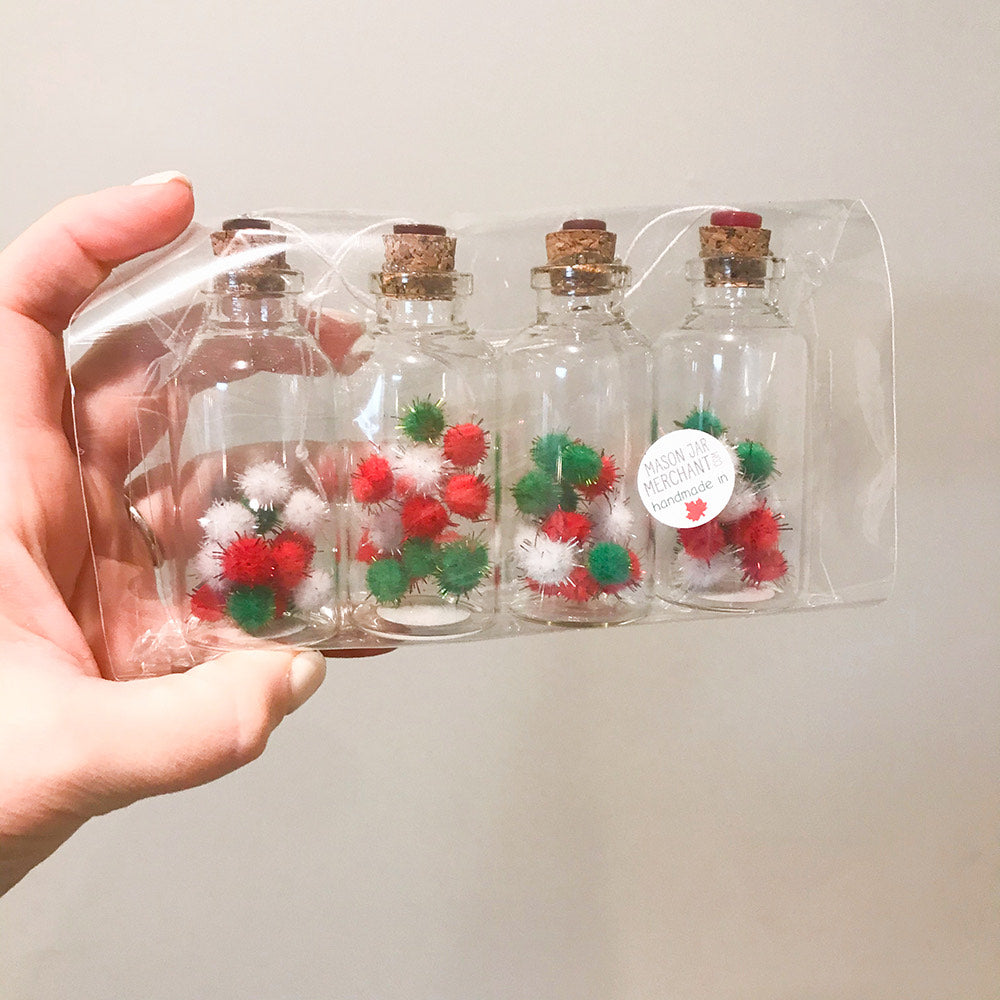 a hand holds four glass jar ornaments sit in a line with cork toppers in a plastic bag. in each jar are a bunch of white, green and red sparkly fluff balls