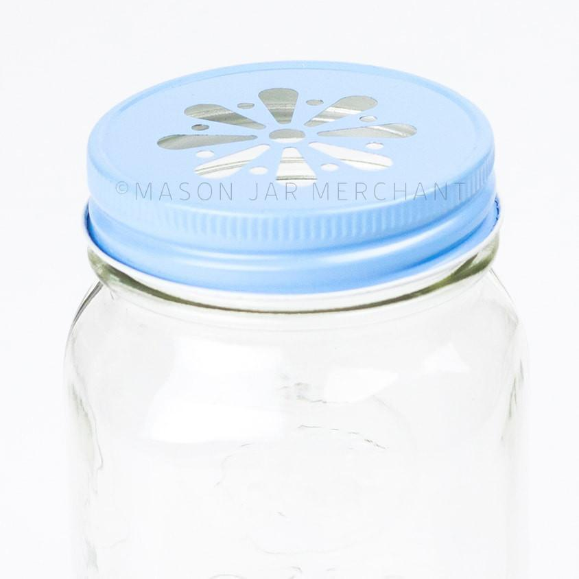 Closeup of baby blue daisy lid on a regular mouth pint mason jar on a white background.