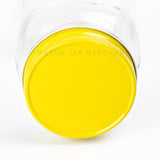 close up of a solid yellow painted lid on a glass mason jar on a white background.
