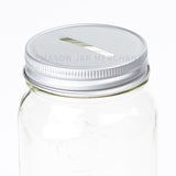 aluminum colored coin slot mason jar lid on a regular mouth mason jar on a white background.