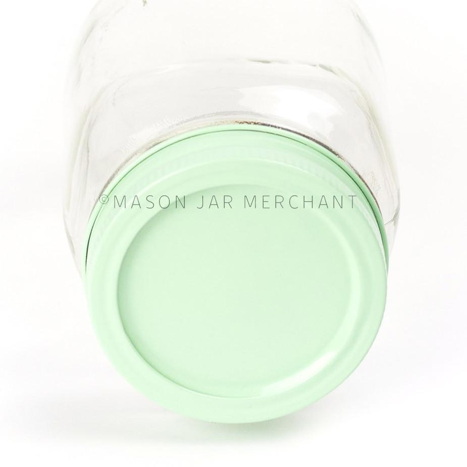 A close up of a regular mouth custom painted lid in mint green on a glass mason jar