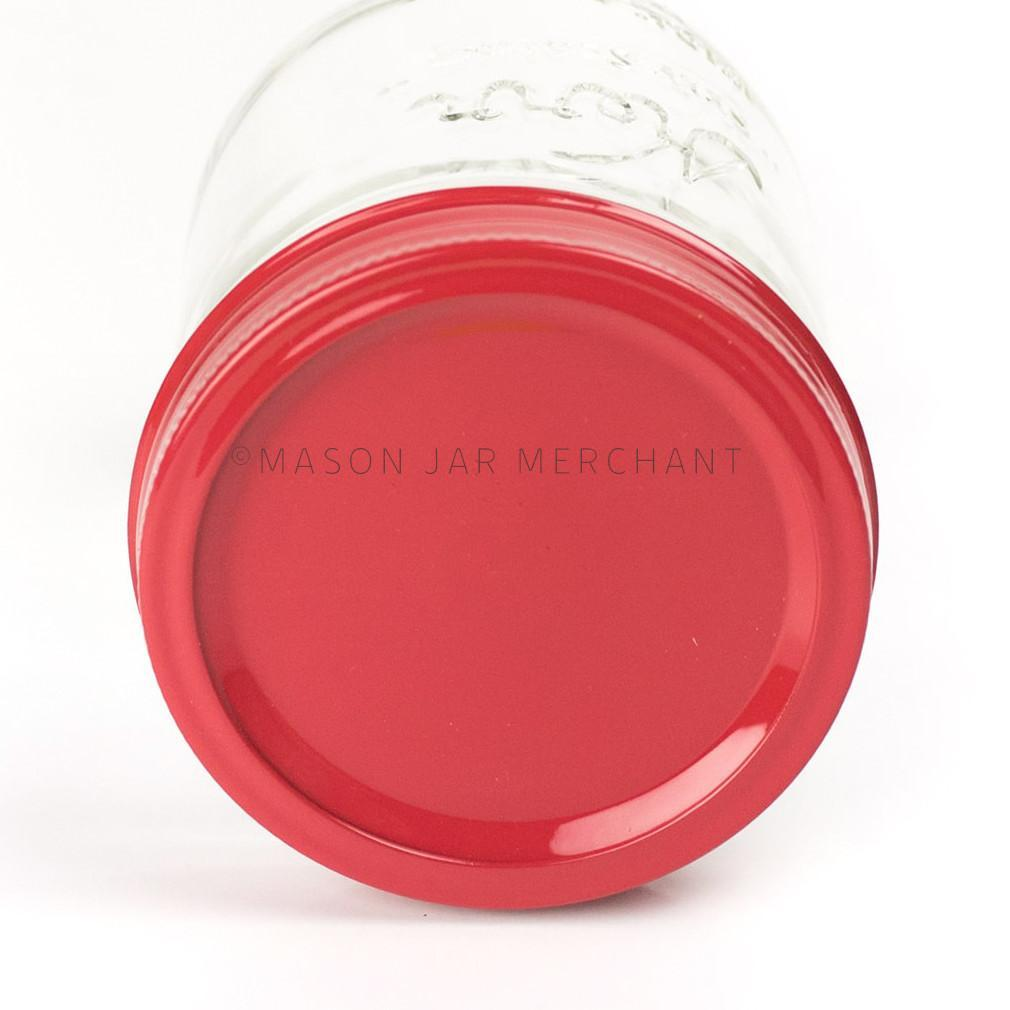 Close-up of a  wide mouth pint mason jar laying on its side against a white background with a red custom painted lid