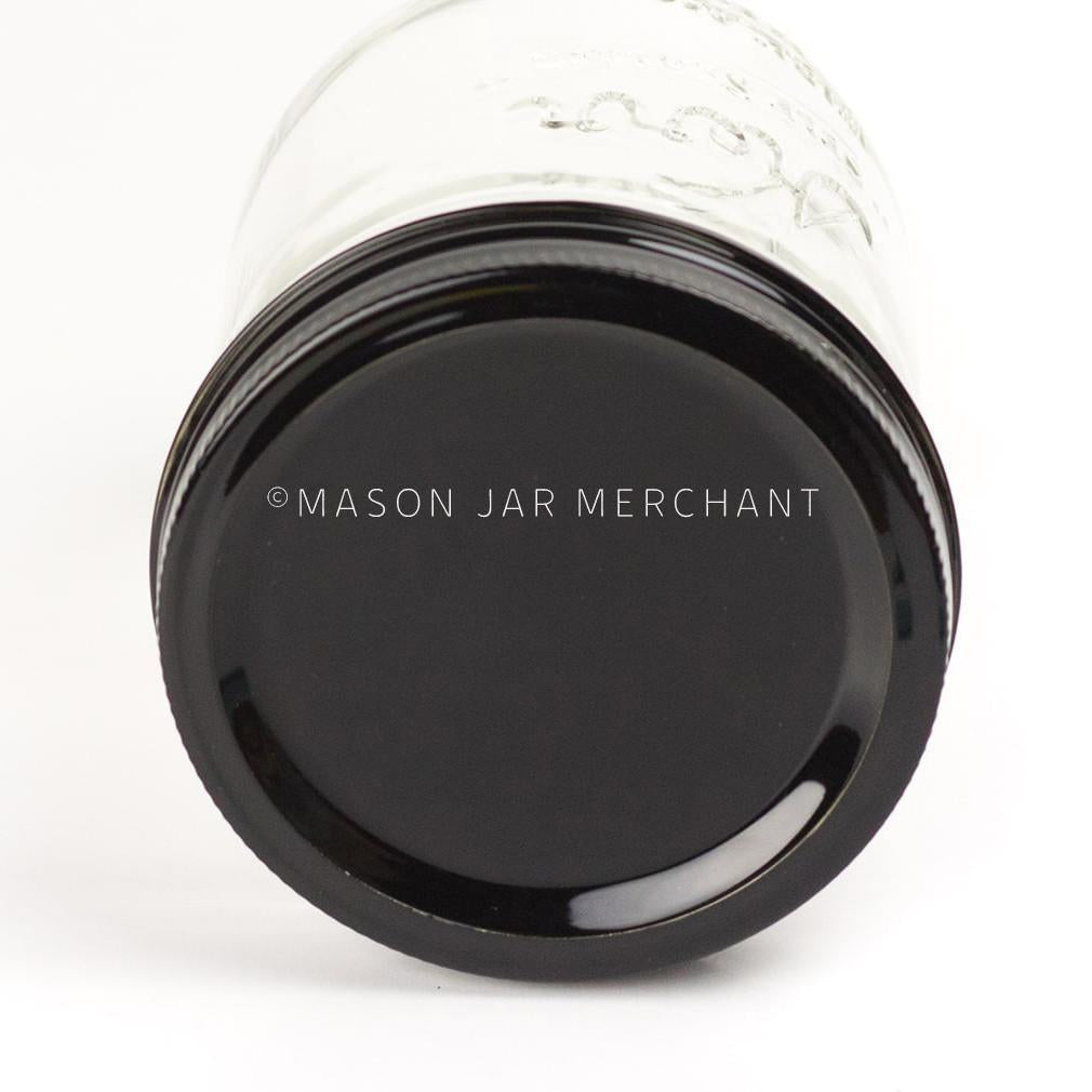 A close up of a black painted lid on a 24 oz reusable glass mason jar tumbler.