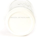 Close-up of a  wide mouth pint mason jar laying on its side against a white background with a cream coloured custom painted lid