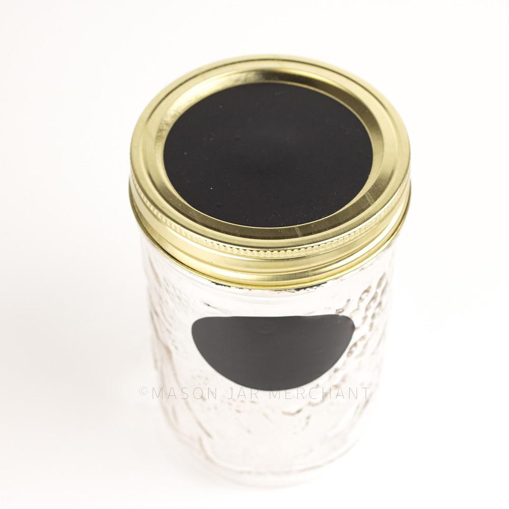 glass reusable mason jar with a gold and chalkboard lid sits on a white background. A 2.5 inch chalkboard circle is on the jar