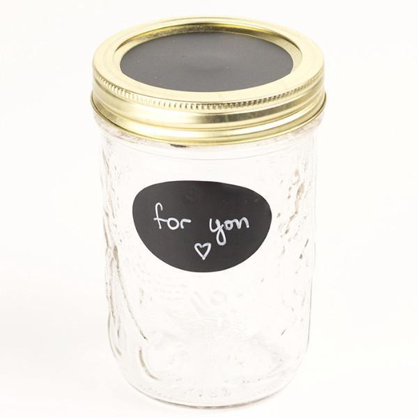 glass reusable mason jar with a gold and black chalkboard lid sits on a white background. On the jar is an oval 2.25 inch black chalkboard label
