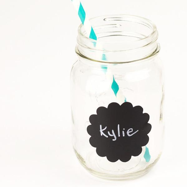 16 oz glass reusable mason jar with a teal and white stripped paper straw sits on a white background. On the jar is a 2.5 inch scalloped circle chalkboard label