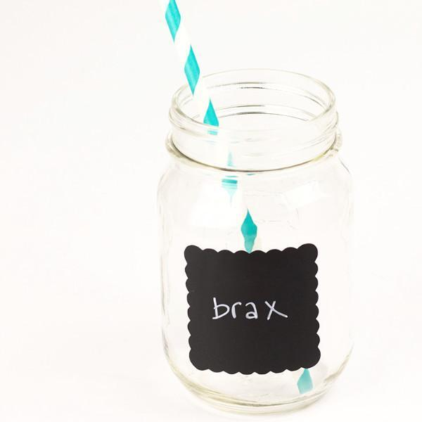 16 oz glass reusable mason jar with a teal and white stripped paper straw sits on a white background. On the jar is a 2.25 inch scalloped square black chalkboard label