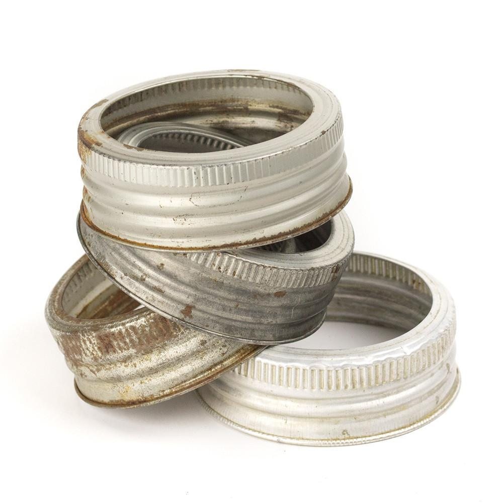 stack of four vintage aluminum GEM mouth mason jar rings on a white background
