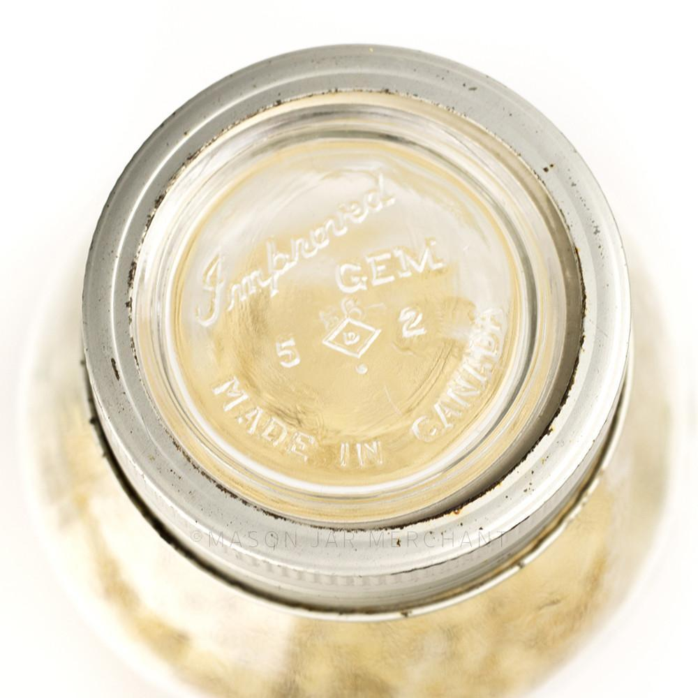 close up of the top of a Gem jar glass lid and metal ring on a glass reusable mason jar on a white background